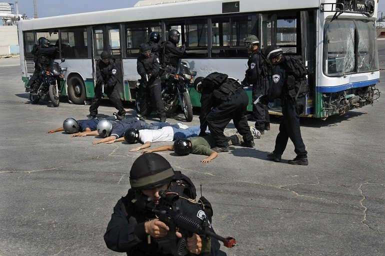 SWAT team members surround people outside of a bus.